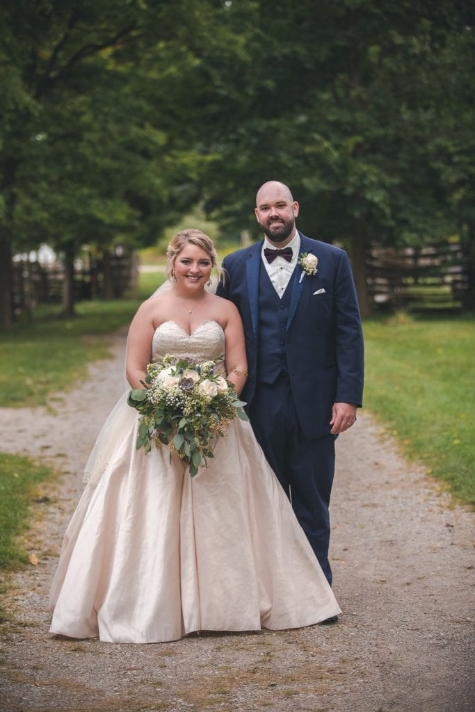 bride and groom standing on a path in front of the fanshawe pioneer village buildings