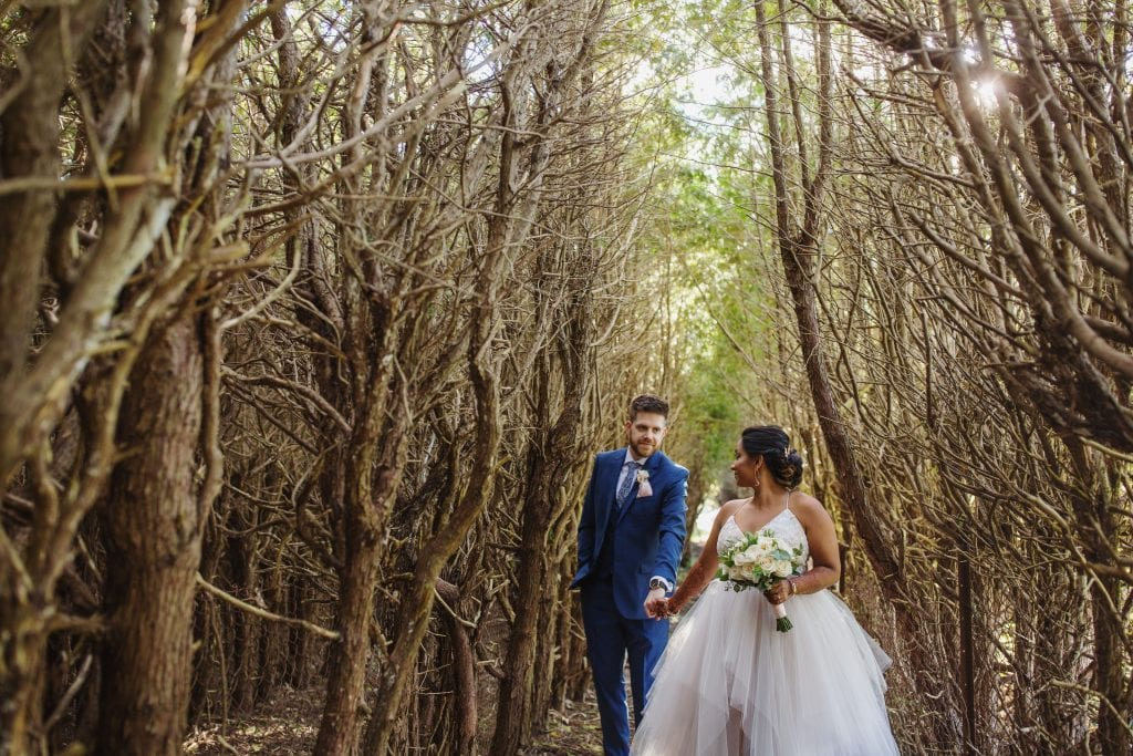 bride and groom walking through the forest