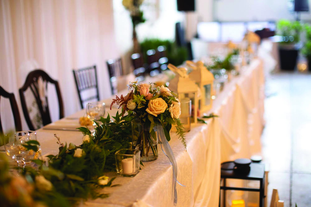 classic neutral wedding decor with long head table and lush florals