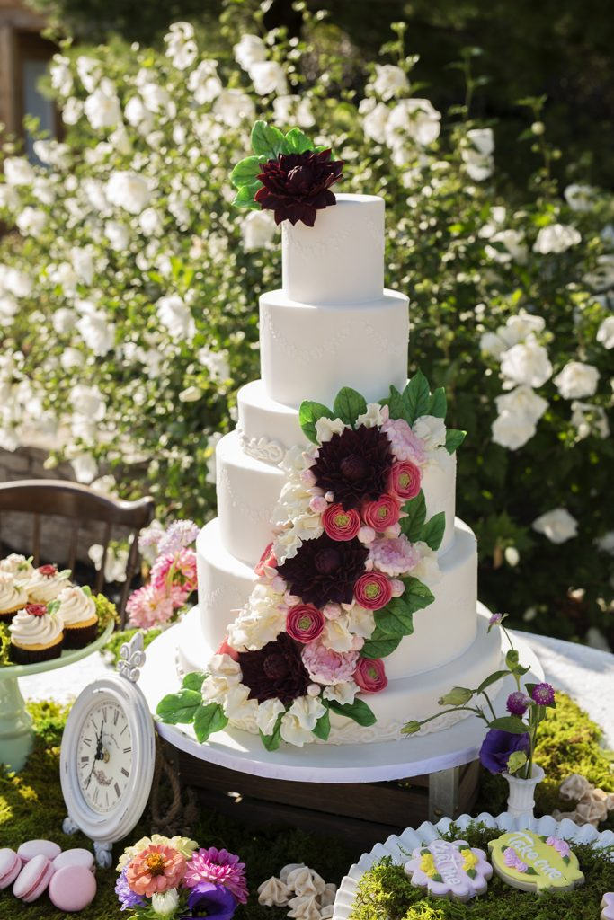 white wedding cake with red, white and black flowers
