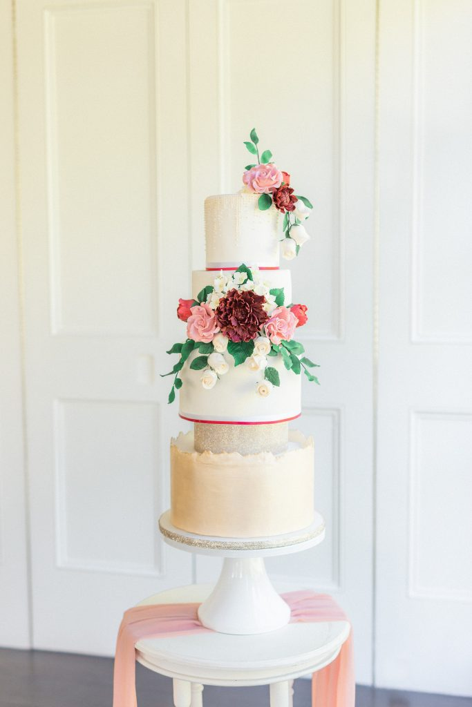 Beautiful champagne cake with a unique live edge bottom tier, and covered in a beautiful arrangement of burgundy and blush sugar flowers.