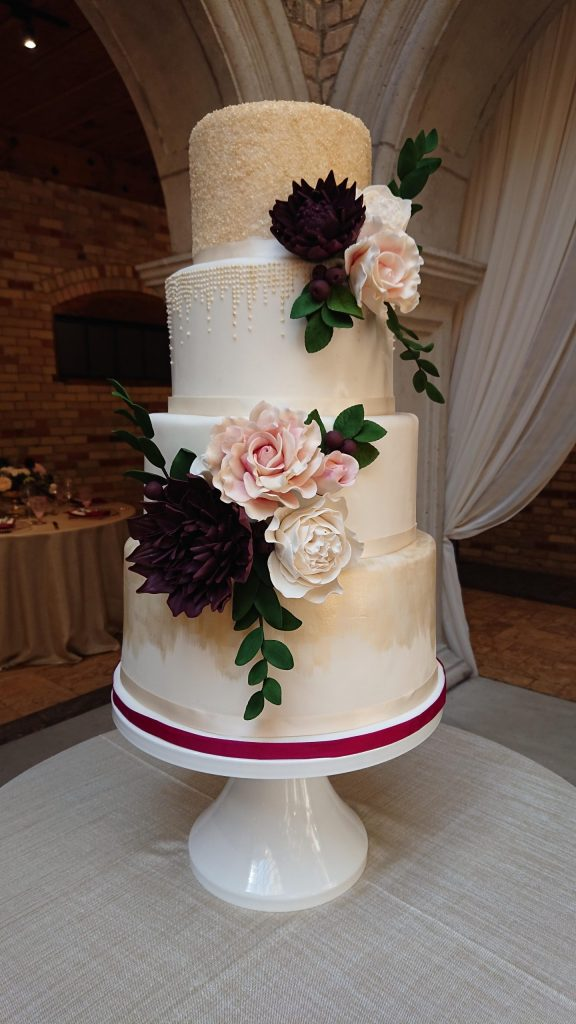 - This 4 Tiered beauty is covered in fine detail, from the bottom painted tier to the piped royal icing cascades on the third tier to the glittery top, all in a beautiful custom champagne tone, and accented with sugar flowers in a deep burgundy, blush and ivory.
