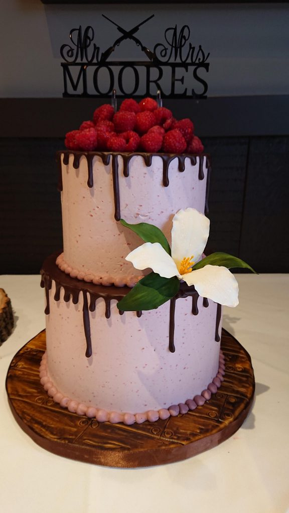 This beautiful woodsy themed buttercream drip cake is topped with fresh raspberries, & beautiful sugar trillium & finished with a hand carved and stained fondant faux wood cake board.