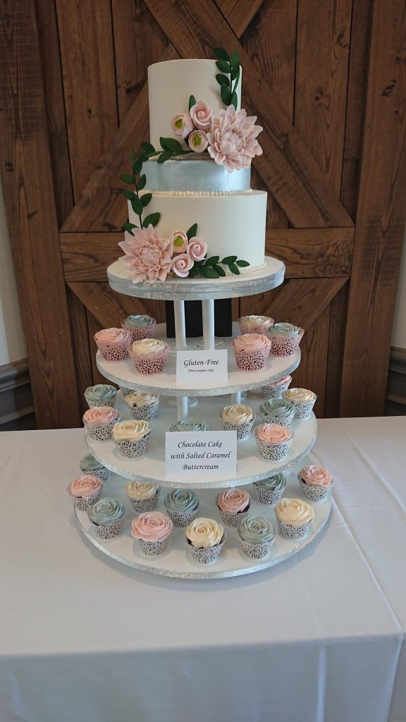 A beautiful sugar flower accented 3 tier cake tops this blush and silver cupcake tower.