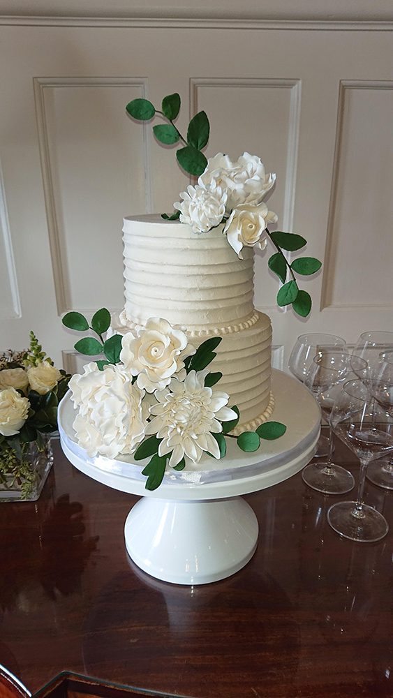 This is a classic white buttercream cake with a horizontal rustic finish, complete with our signature handmade sugar flowers.