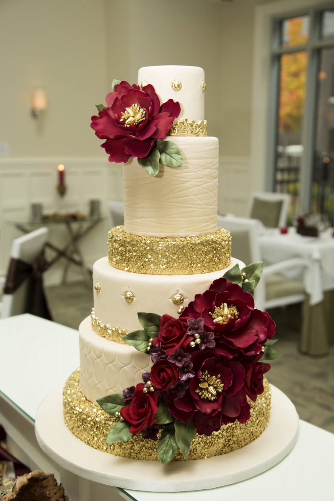 Gold sequins and bugundy peonies adorn this elegant cake.