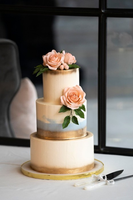 Beautiful blush roses adorn this all buttercream cake with touches of blue and gold.