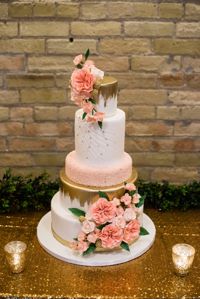 Soft blush and gold, featuring sugar roses and greenery.