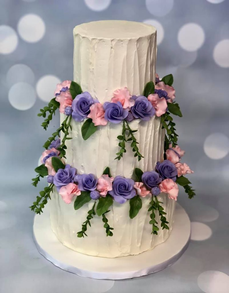 Delicate pink and purple sugar flowers and cascading greenery surround this buttercream beauty.