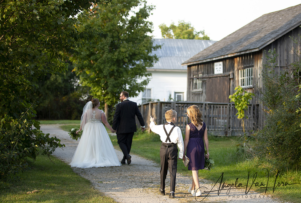 bride, groom and two children walk down a path beside the renaud orange lodge at fanshawe pioneer village