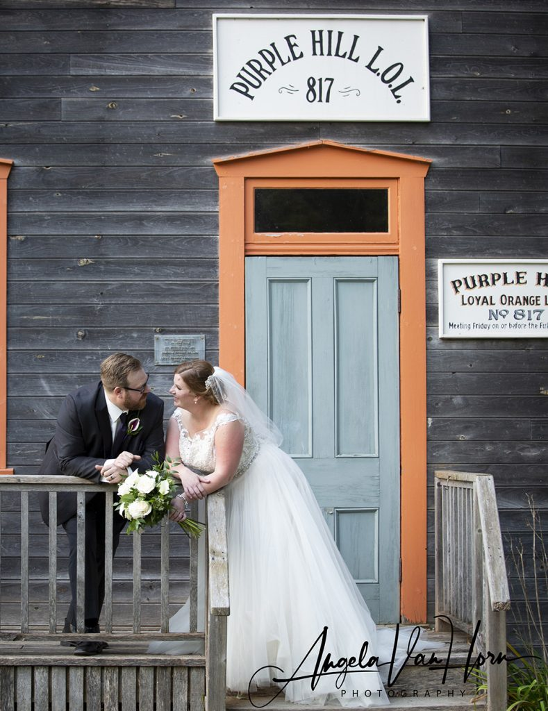 bride and groom standing in front of the old renaud orange lodge at fanshawe pioneer village