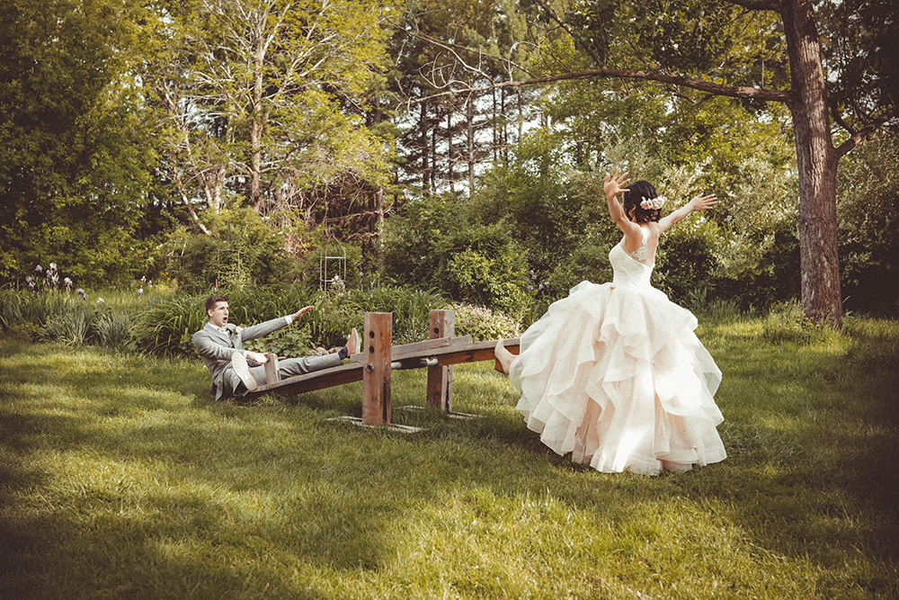 bride and groom having fun on a teeter toter