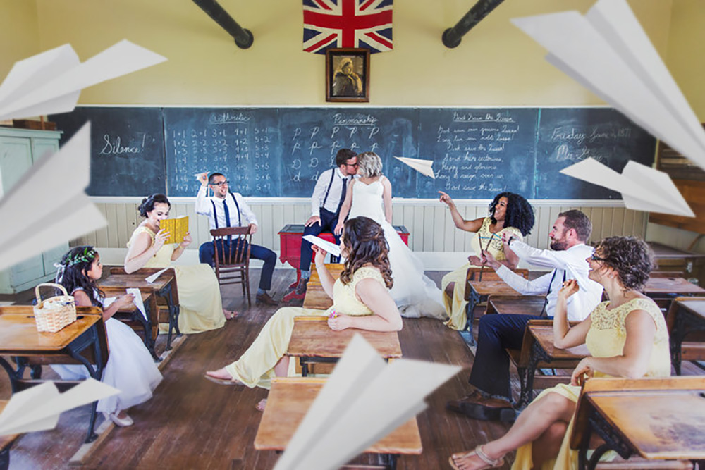 bride and groom kissing in the fanshawe pioneer village school house with their wedding party throwing paper airplanes at them