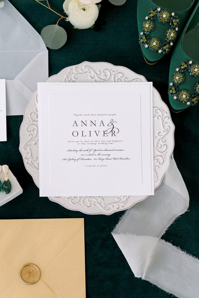 crisp clean white invitation with emerald green shoes and earrings
