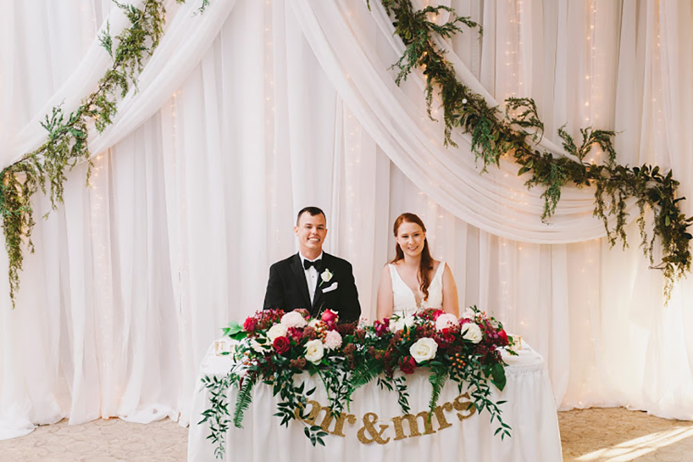 wedding sweatheart table with white  backdrop, greenery and lush flowers now & always