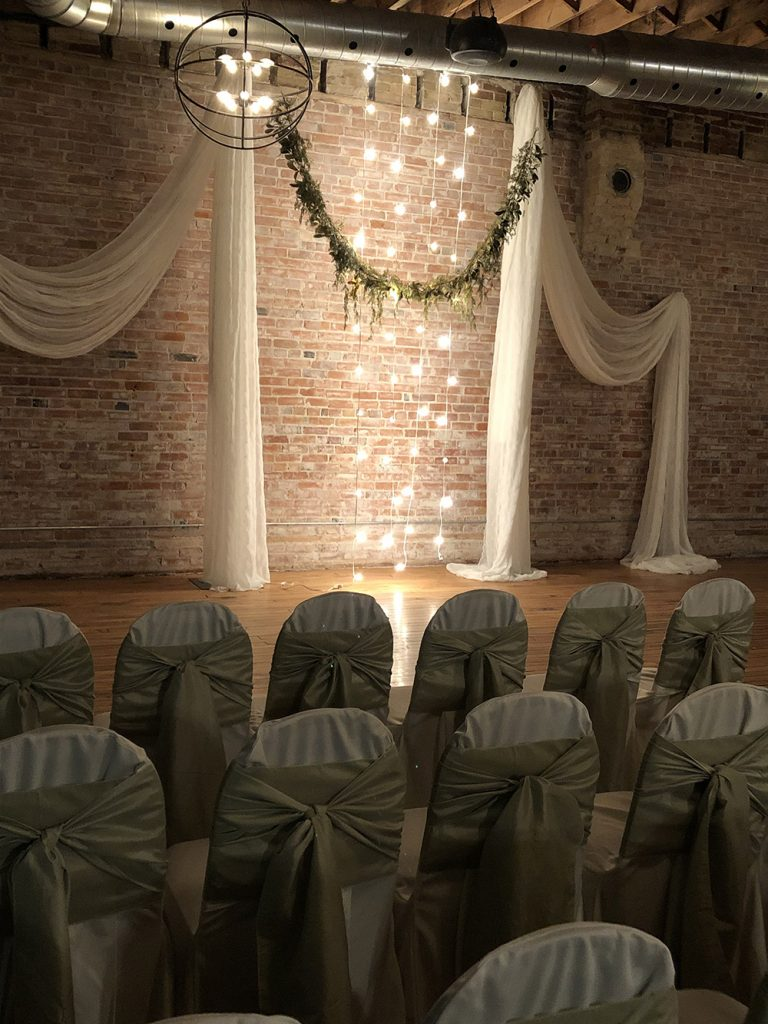 brick wall wedding ceremony decor with pillars, lights and greenery now & always