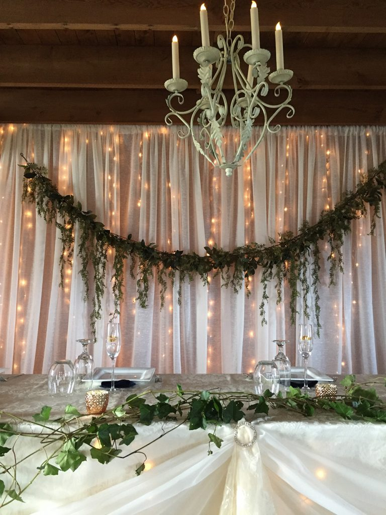 head table with white backdrop with lights and greenery
