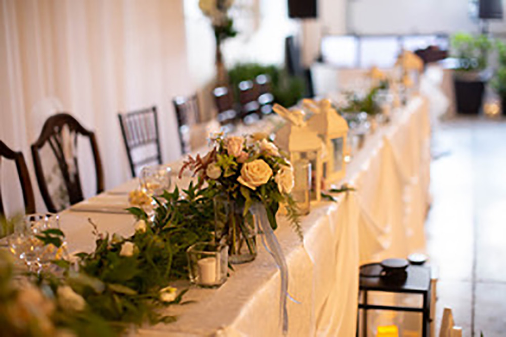 head table with flowers and greenery now & always