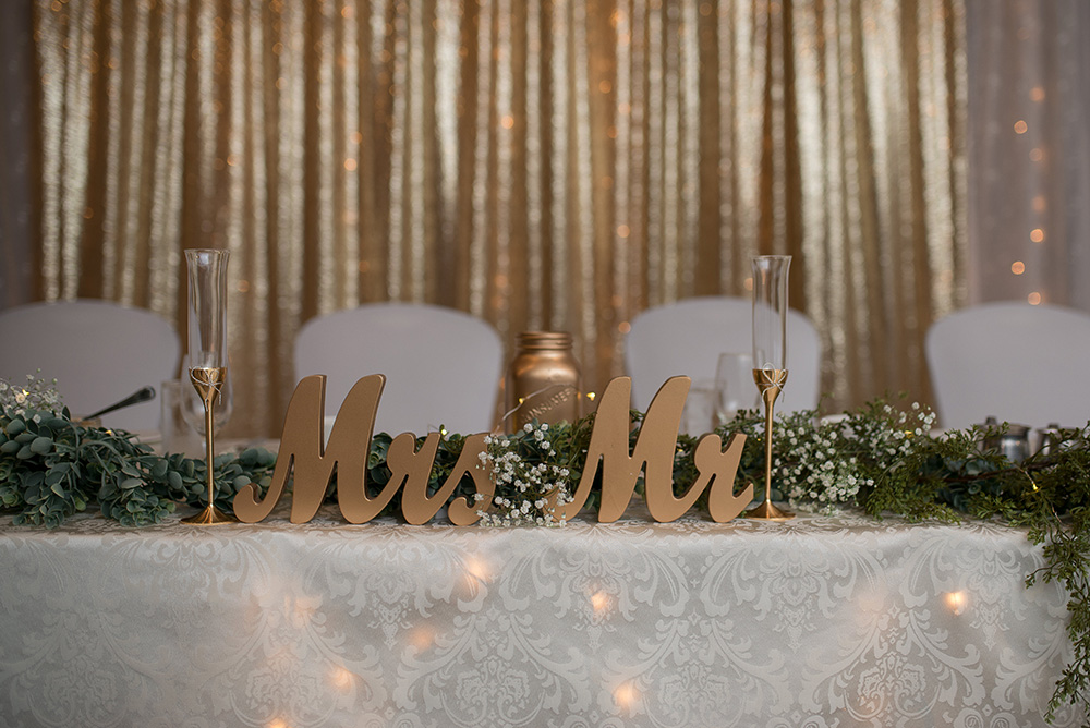 sweatheart table with gold mr & Mrs letters and gold backdrop