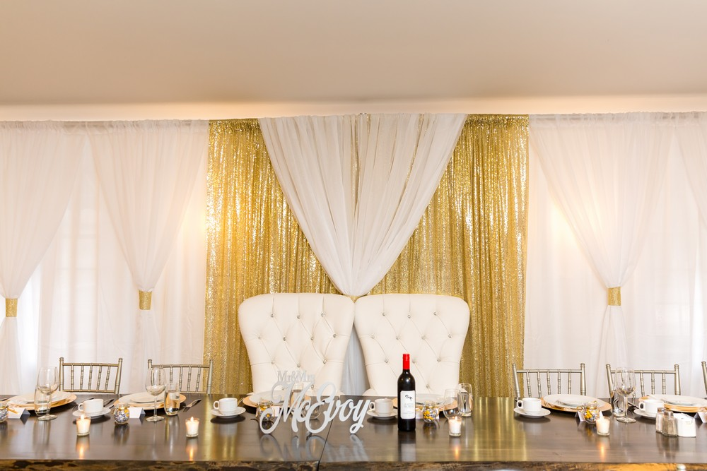 gold and white backdrop behind a head table with king and queen chairs