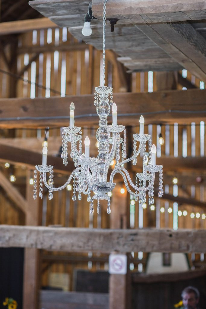 gorgeous crystal chandelier hanging from barn rafters