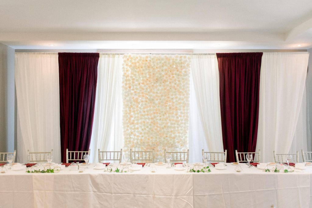 headtable backdrop with floral fabric in the centre and burgundy fabric on the ends