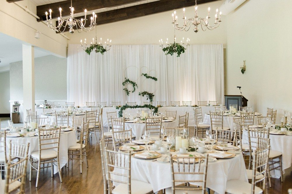 Stratford Country Club setup with round tables with white table cloths, gold chiavari chairs, gold hanging candelabras with a fabric backdrop with gold hanging hoops lining the head table
